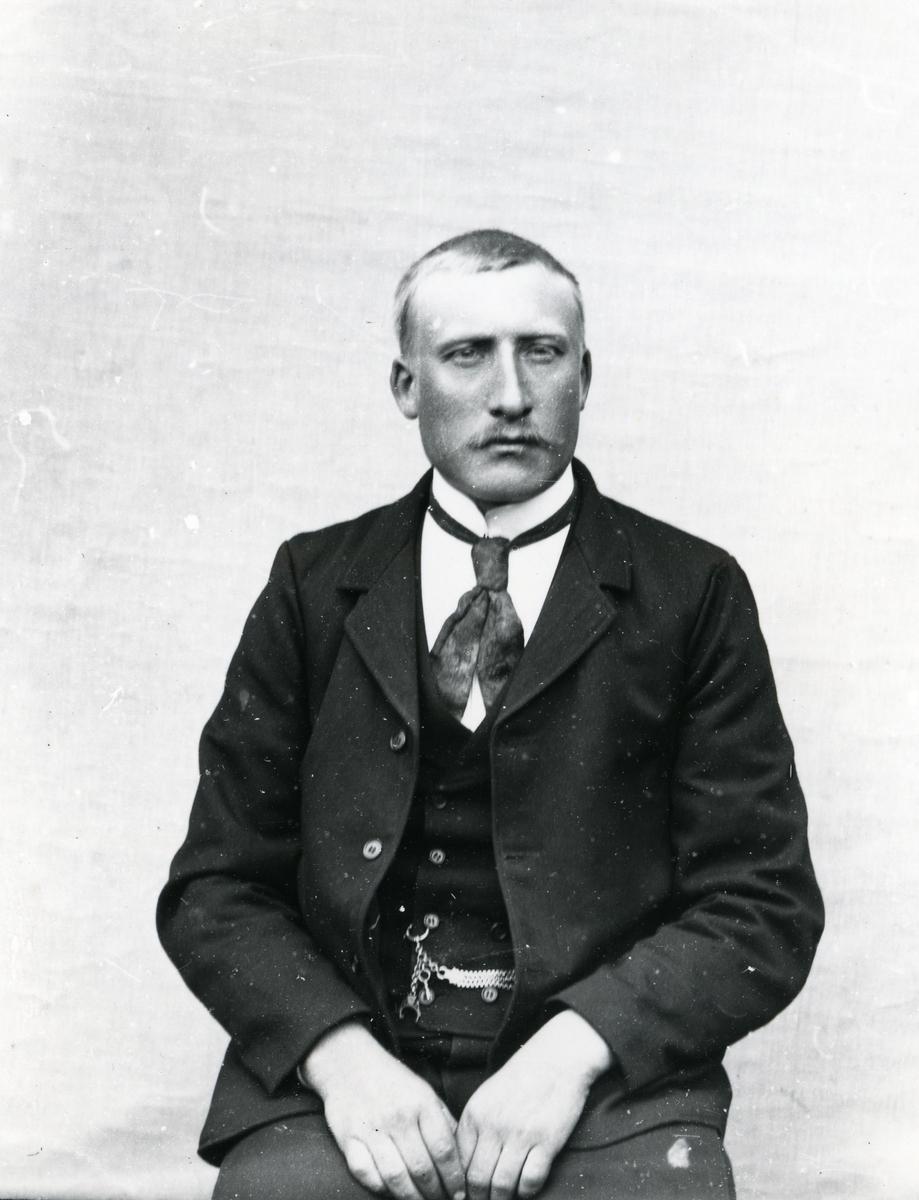 Dresskledd mann i halvfigur, sittende foran lerret