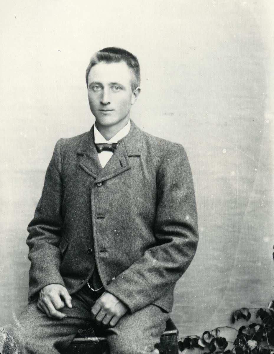 Dresskledd mann, sittende foran lerret