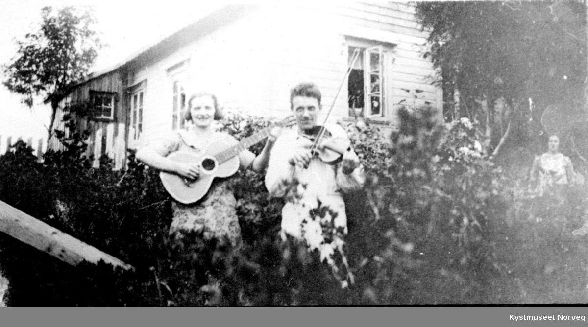 Ungdommer spiller gitar og fele i en hage.