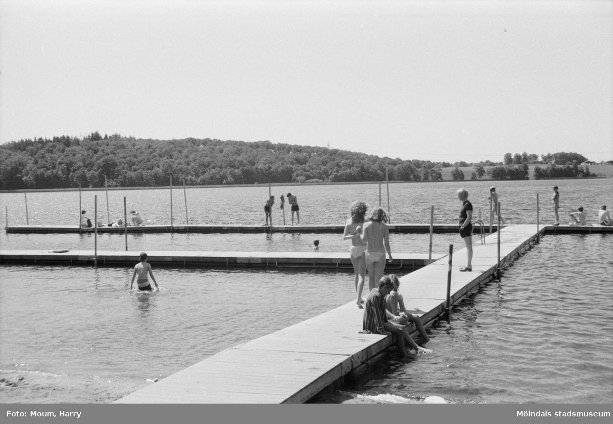 Människor som badar vid en badplats, år 1984, möjligen Tulebosjön i Kållered. Fotografi taget av Harry Moum, HUM, Mölndals-Posten.