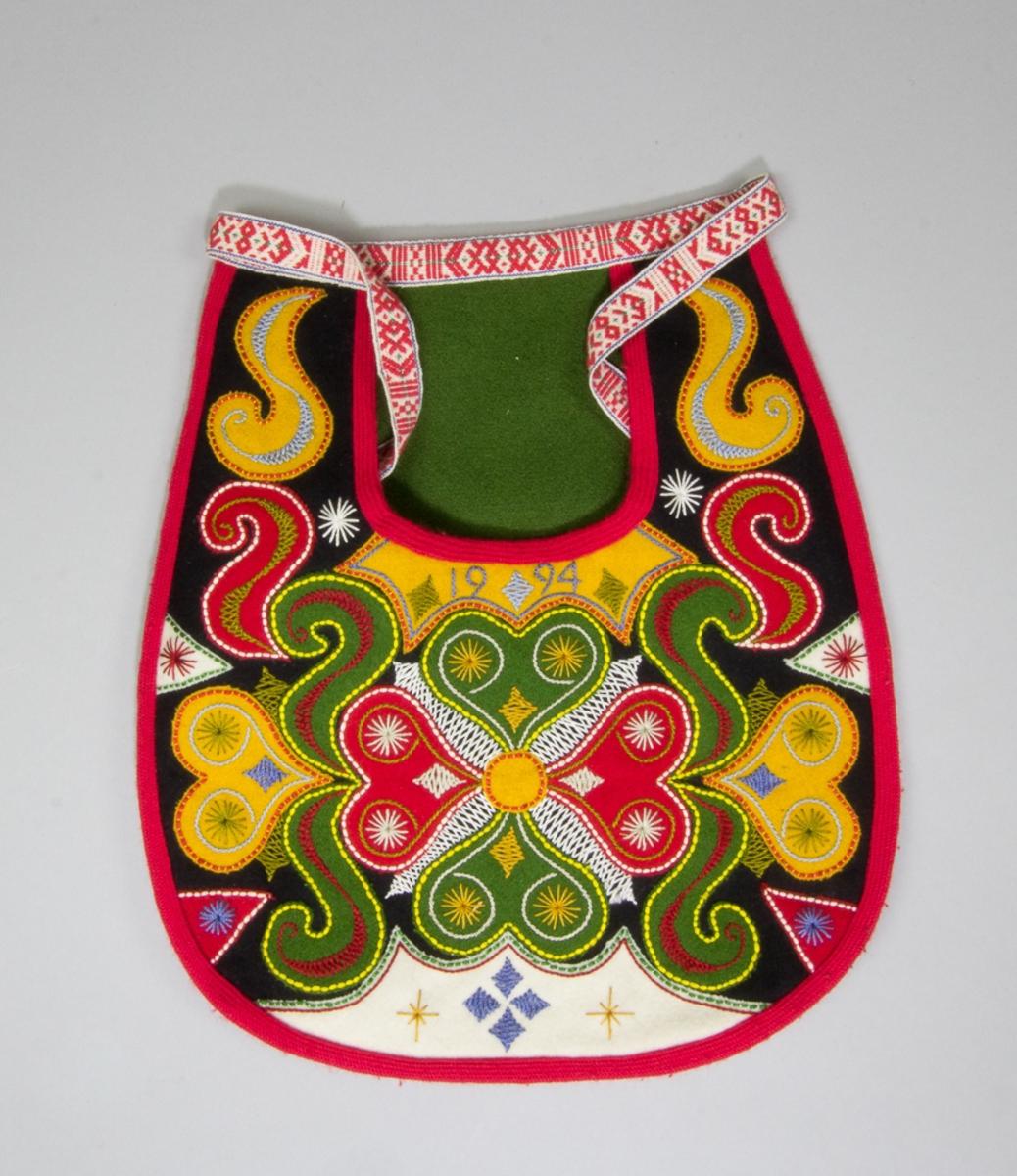 Kjolsäck till dräkt för kvinna från Leksands socken, Dalarna. Modell med u-formad öppning för handen. Tillverkad av svart ylletyg, kläde, med applikationer av kläde i rött, grönt, gult och vitt, hjärtformat motiv i mitten och s-formade figurer runtom. Broderier i flera färger både på och mellan applikationerna, ullgarn och bomullsgarn, läggsöm för att fästa ner applikationerna och dessutom flätsöm, stjälksöm och sticksöm. Under öppningen årtalet 1994 broderat med stjälksöm. Kantad med rött diagonalvävt band av ull. Foder av vitt bomullstyg, tuskaftsvävt. I öppningen fäst en spegel av en bit grönt kläde. Baksida av svart kläde. Midjeband av fabriksvävt band av bomull med mönster i rött på vit botten, knäppt med modern hake och trådtränsar.