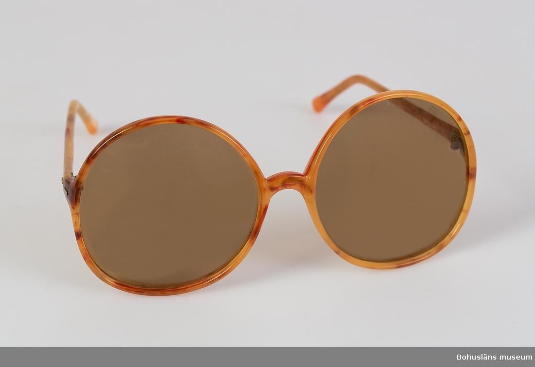 Solglasögon med båge av plast i gulbrun imiterad sköldpadd, bruna. Polaroidglas, stora och runda. Bågen tillverkad i Italien. Inköpta  i Uddevalla omkring 1970. Glasögonfodral i form av påse som dras ihop på kortsidan med ett tvinnat snöre av konstfiber. Fodralet är av beige mockaimitation, på insidan  märkt LOZZA.