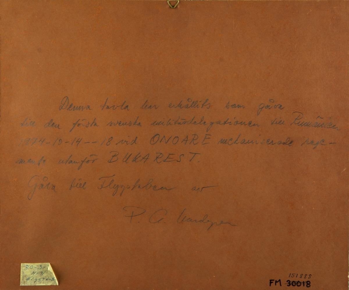 Inramad Tavelrelief. Tavlan föreställer en pansarvagn och två militärer med gevär. På baksidan av tavlan står: Denna tavla har erhållits som gåva till den första Svenska militärdeligationen till Rumänien 1974-10-14--18 vid ONOARE mekaniserade regemente utanför BUKAREST. Gåva till Flygstaben av P.G. Lundgren.