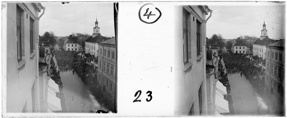 'Bildtext: ''Demonstrationståg 1 maj.'' :: Gatuvy med folkmassa, åskådare, längs gata med hus och ev. kyrka, torg. På gatan går demonstrationståg. ::  :: Ingår i serie med fotonr. 5259:1-16. Se även hela serien med fotonr. 5237-5267.'