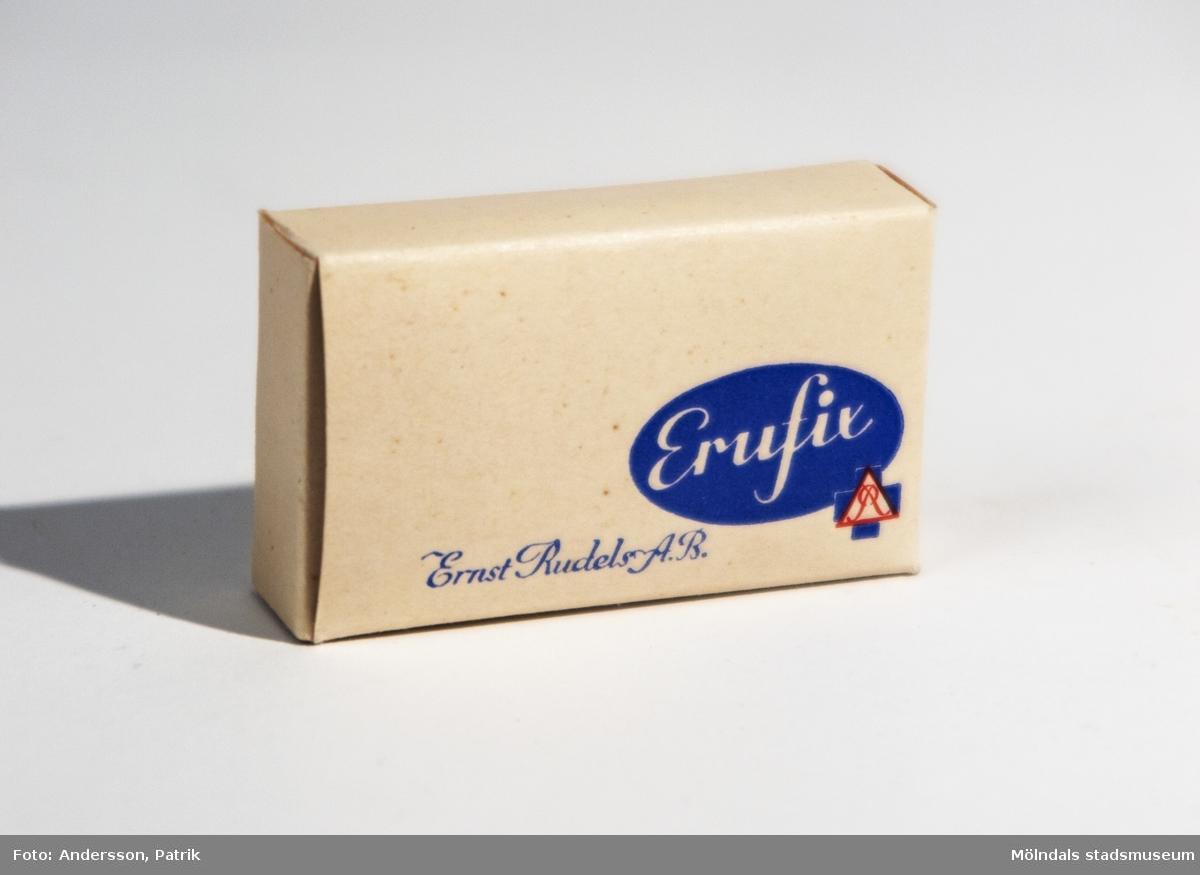 Dambinda i pappförpackning, tillverkad av Ersnt Rudels AB. Bak på förpackningen finns en bruksanvisning för hur man använder bindan, tryckt på förpackningen. Förpackningen ser oöppnad ut.