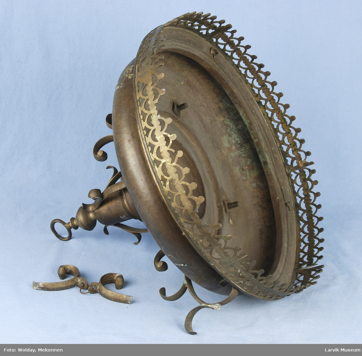 Form: sirkulær, prof.skål med gj.br.kant. opphengt i 4 gjennombrutte, ornerte lenker.