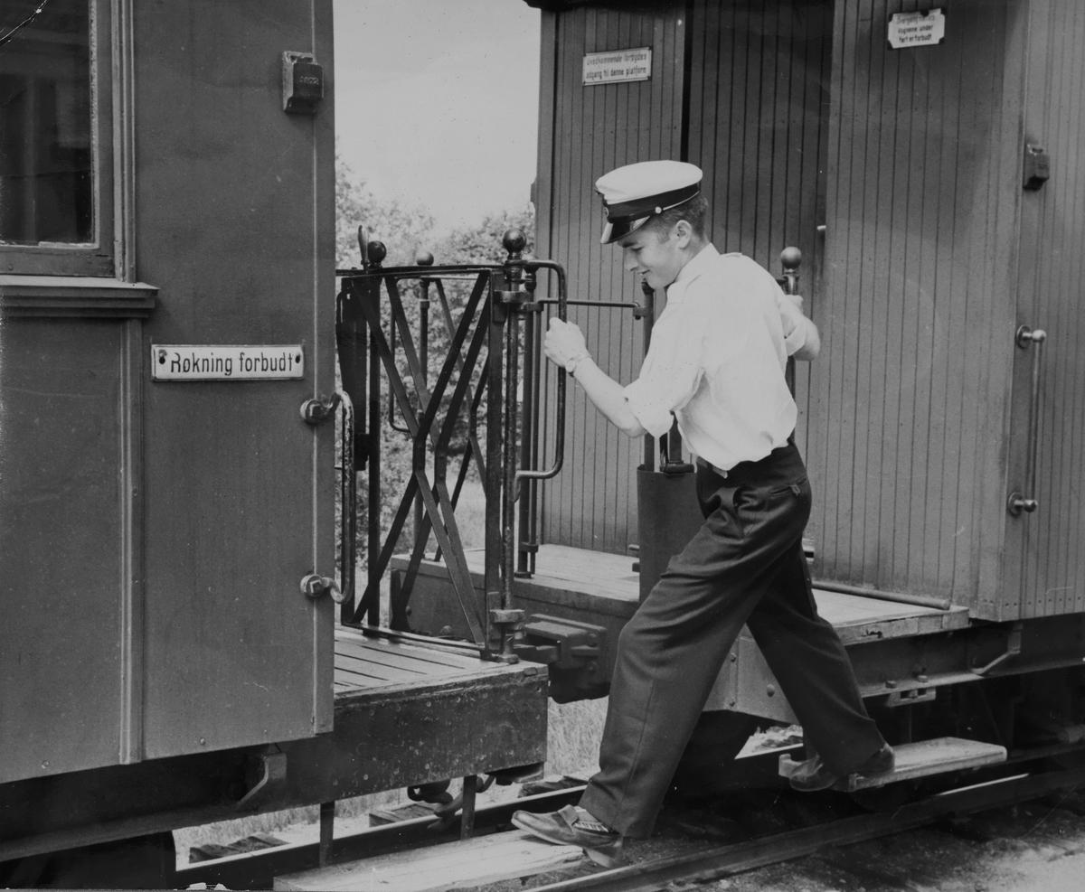 Ung konduktøraspirant går fra vogn til vogn for å kontrollere billetter.