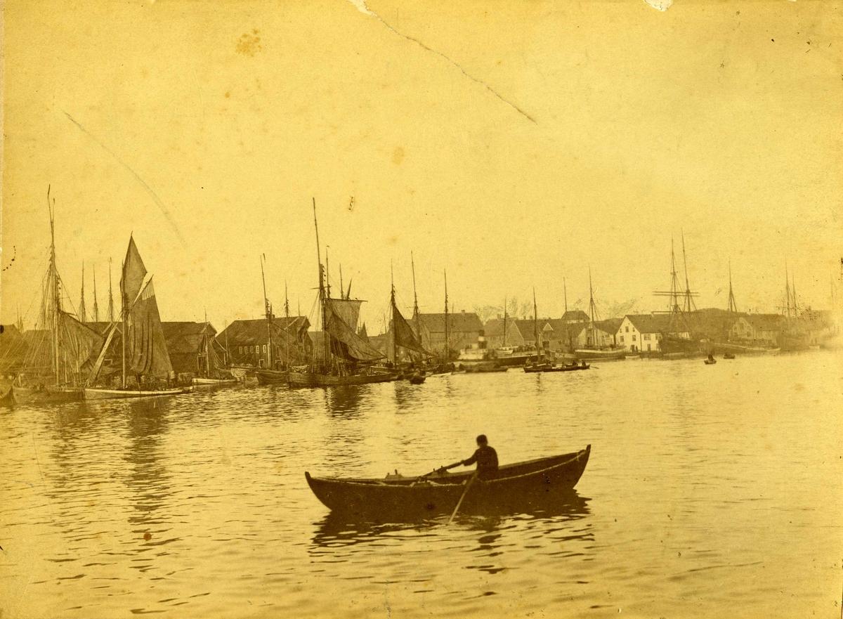 Havn - småfartøy En robåt i Smedasunddet. Lenger bak seilbåter langs land. Flere sjøhus bak seilbåtene. Risøy med Kortanes i bakgrunnen.