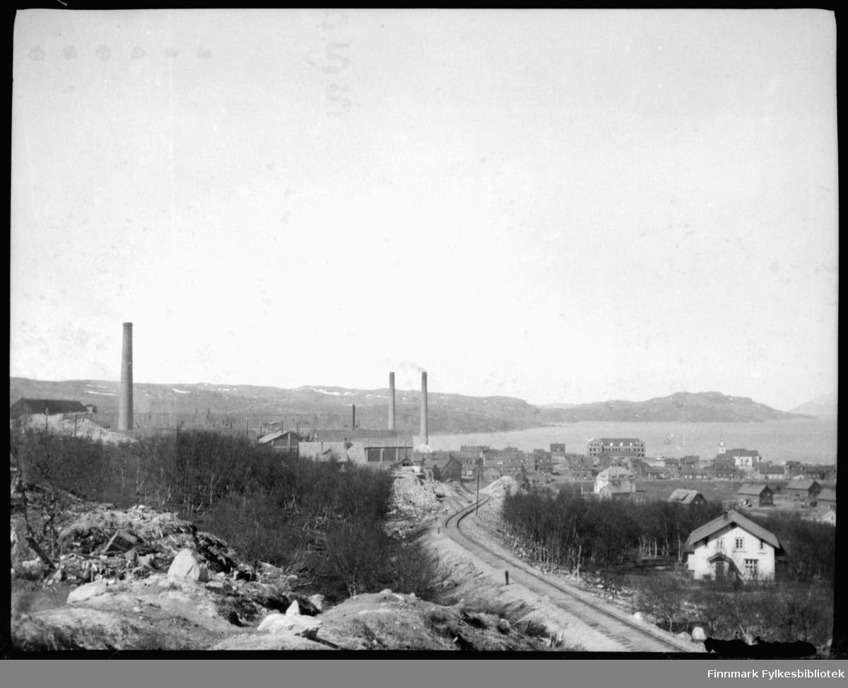 Anrikningsverket i Kirkenes fotografert på våren. Foran i bildet jernbane og noen arbeiderboliger.