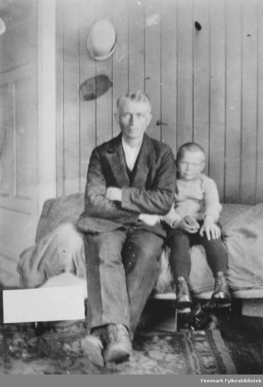 Andreas Sivertsen og sønnen Sivert sitter på en seng. Bildet er tatt i kammerset i våningshuset på gården Veines, Øvre Neiden