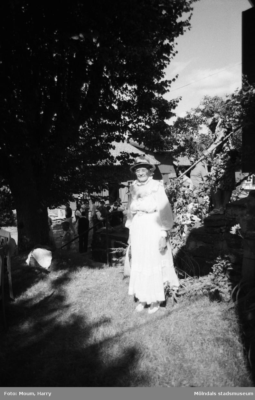 """Lindome Hembygdsgille firar 20-årsjubileum på Börjesgården i Hällesåker den 23 juli år 1983. """"Alice Karlsson som Mamsell Therese i vit klänning från sekelskiftet med tillhörande stråhatt.""""  För mer information om bilden se under tilläggsinformation."""