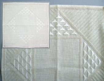 """En broderad duk och ett broderiprov i linne. Broderi i rätlinjig plattsöm och myrgång i blekt lingarn på blekt linneväv. Geometriskt mönster; trianglar och diagonala linjer. WLHF-0466:1 Broderiprov. Mått 140 x 180 mm. Tunnare kvalité.WLHF-0466:2 Färdig duk. Mått 320 x 310 mm. Märkt med en lapp med texten: """"Isblomma modell 144:- material 25.50"""". Grövre kvalité. På bild, bilden är ett montage med den färdiga duken samt detalj. Inte så vit i verkligheten. WLHF-0466:3 Färdig duk. Mått 330x320 mm. Något ljusare och lite större än :2. Märkt tygetikett  """"Hemslöjd-Föreningen Leksand"""" och etikett """"Leksands Hemslöjds-vänner"""" samt pappetikett """"Leksands Hemslöjdsförening  """"Isblomma Skollinne II Pris: Matr 146:-""""Mönsterskiss på rutpapper finns tillsammans med broderiprovet.Scannad till datamapp: """"Tillbehör""""."""
