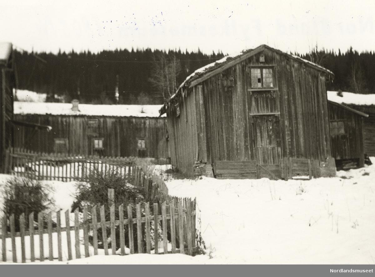 Rødfjell, Rana. Gammel bygning, eier Arnold Thommassen, stående bordkledning, vindu med vindusprosser, smårutet, torvtak. Flere bygninger i bakgrunnen, hagegjerde i forgrunnen. Snø på bakken.