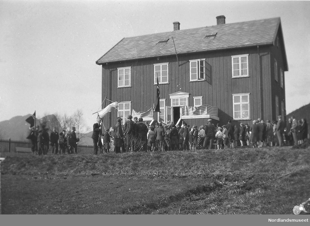 Mange barn og noen voksne midt på bildet. Store og små flagg. En mann som holder i en fane. Stort hus midt på bildet.