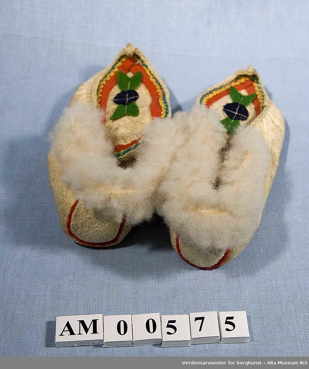 Et par tøfler av lammeskinn. Dekorert med biter av rødt, grønt og blått klede samt gule kroklisser og grønn søm på overstykket. De to tøflene er festet sammen med en tråd.