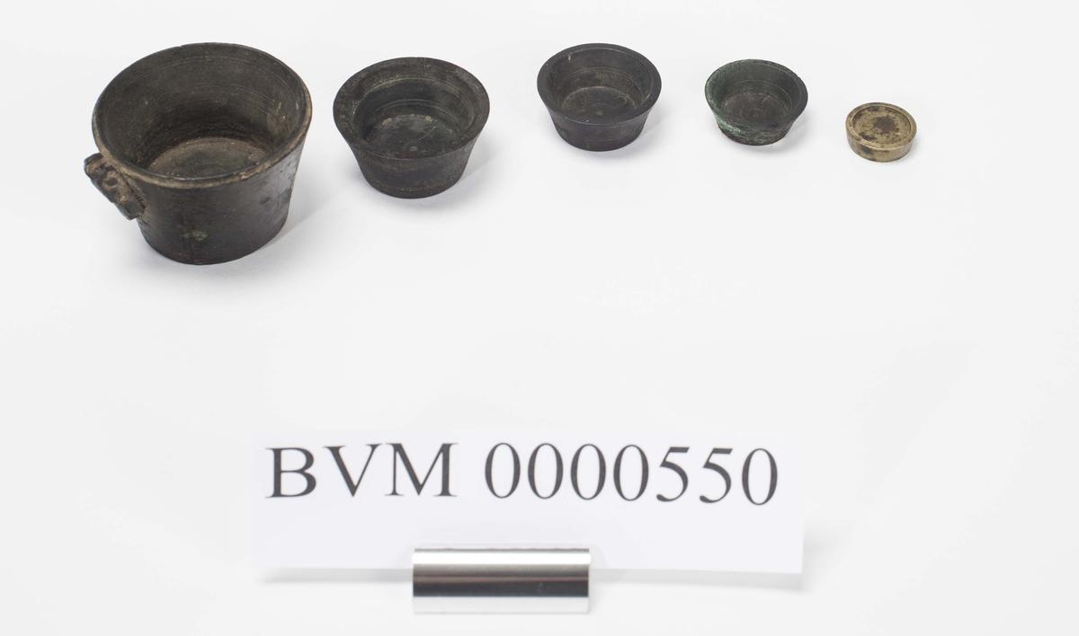 Samling av fem lodd. De fire største er av jern, det minste av messing. Det største loddet mangler opprinnelig lokk.   Høyde og diameter fra det største til det minste er: 1: h. 3,8 cm, dia. 5,0 cm. 2: h. 1,8 cm, dia. 3,6 cm. 3: h. 1,3 cm, dia. 3,0 cm. 4: h. 1,0 cm, dia. 2,5 cm. 5: h. 0,3 cm, dia. 1,8 cm.