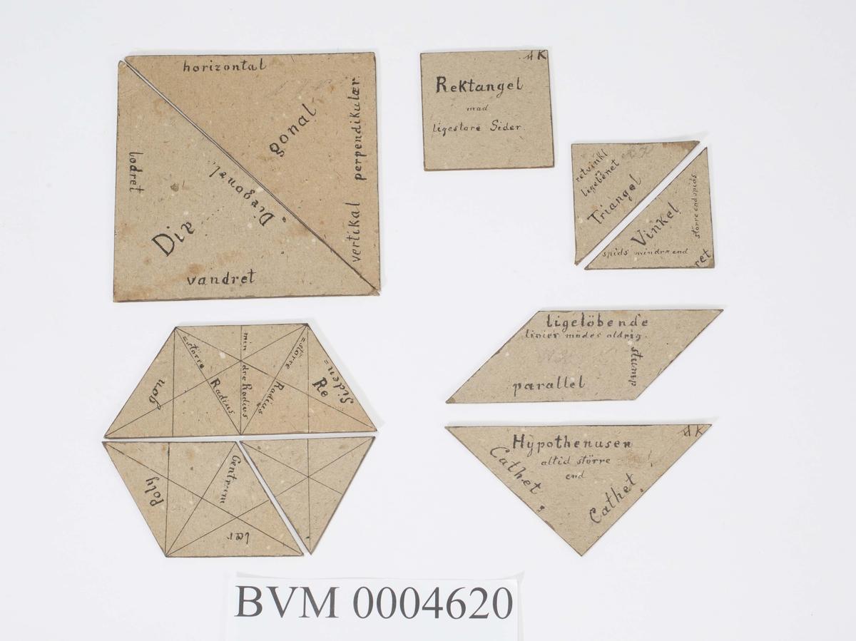 Diverse geometriske figurer i papp. På figurene er skrevet en del geometriske begreper som grunnlinje, trapes, rombe, parallell osv.