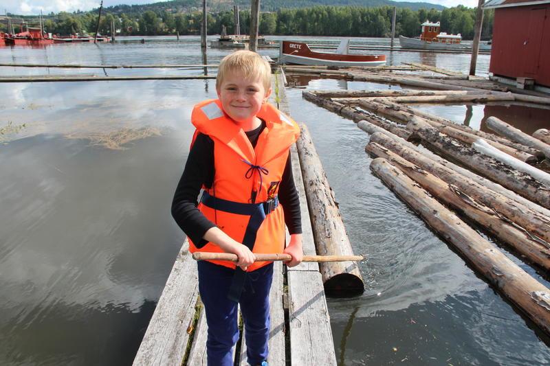 Gutt med redningsvest bruker fløterhake på tømmeret i elva