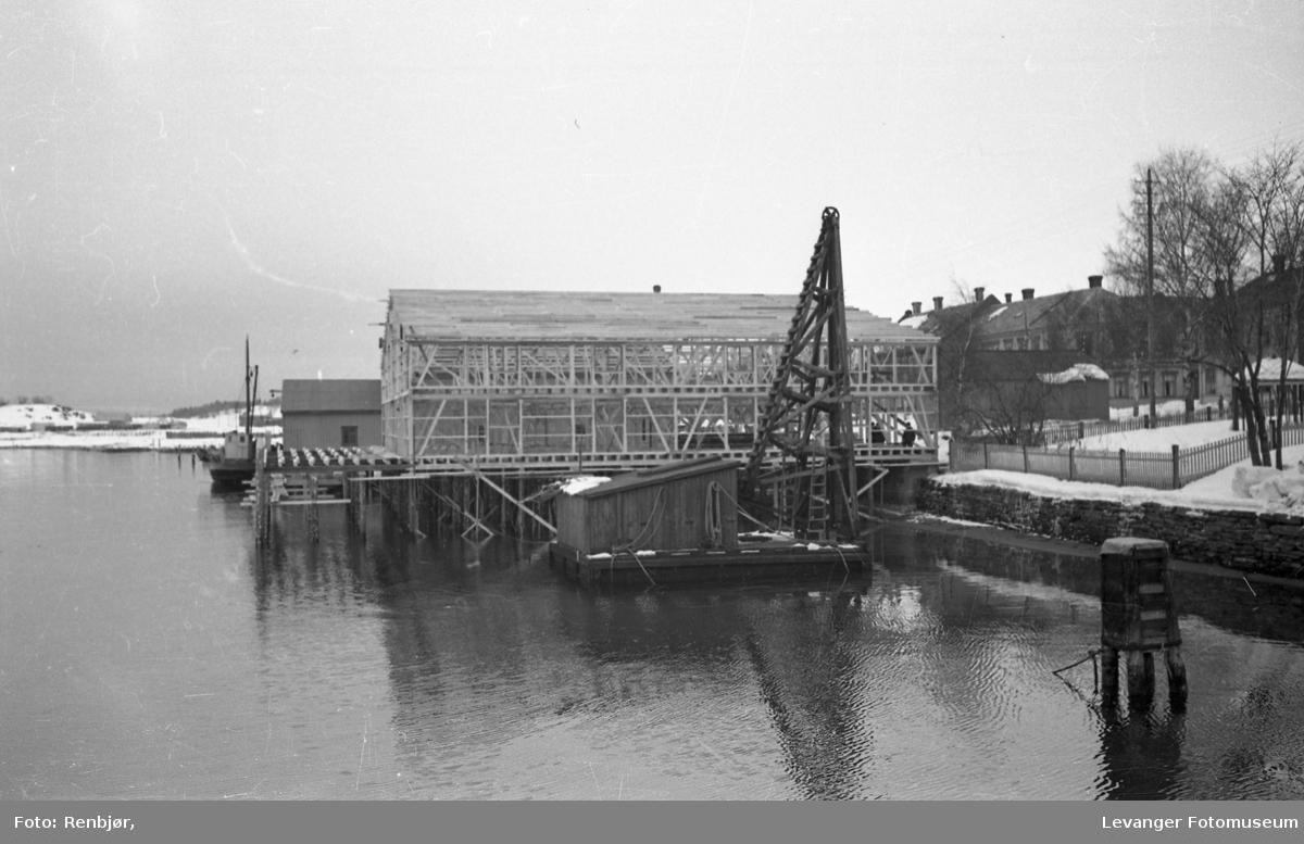 Brygger og hus langsmed Levangersundet. Ole Olsen Øhrens brygge under bygging.