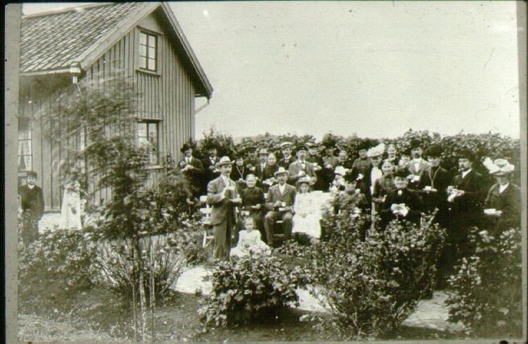 Föreningen Enigheten i Emma Jannes trädgård. Överst raden, fr.v. räknat från husknuten (barnen okända)1. Fiskhandlare Jonsson (Lumpe-Jonsson) 6. Herrn alldeles bakom flickan i vit hatt: Emma Janne (Jacobsson) 11. Fru Malmsten. (nr 4 räknat från höger) 13. Herr Malmsten. 14-15. Liedholms. Första raden, fr.v. 1.? 2. Möjligen  Svea Svensson. Gas-Svenssons fru 3. Gas-Svensson