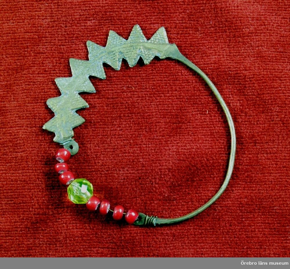 Armband av metall med kristallpärla - slipad och 7 röda pärlor.Gåva a generalmajor Johan Lilliehööks sterbhus delägare.Digitalbild finns.