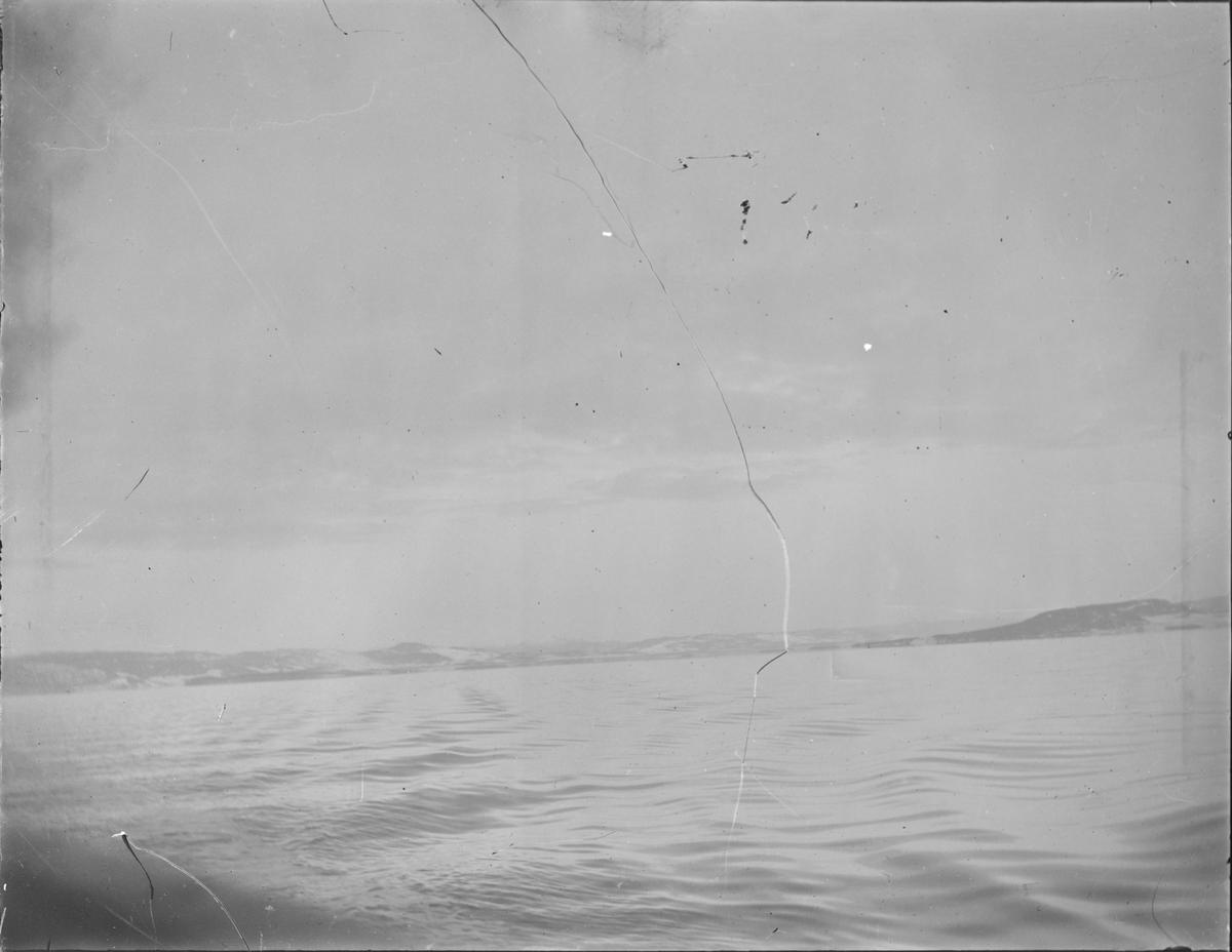Utsikt over vann, mot land. Sjøen ligger rolig bortsett fra bevegelse laget av en båt. Bakenfor sees et jordbrukslandskap med lave åser.