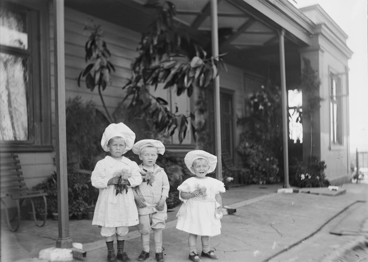 Tre barn står under svalgangen til hovedhuset på Linderud Gård. De holder små blomstebuketter i hendene.