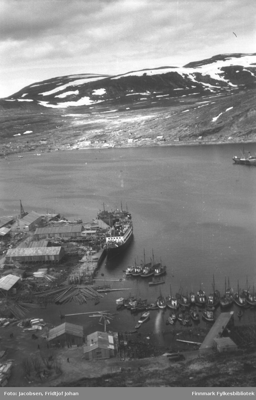 Fotografi av Hammerfest havn tatt fra fjellet Salen. Noen brakker er kommet opp i Strandkanten og på Hammerfest-neset. Brakka nede til høyre på bildet er Mehus' fiskeforretning. En mørk lastebil ses i Strandgata nederst på bildet og flere personer går på veien nede til venstre. Mye tømmer flyter i sjøen ved Verftsfjæra og mange fiskebåter ligger fortøyd i indre havn. Over Verftsfjæra er Nissen-kaia under bygging og ved siden av den ligger hurtigruteskipet Lofoten ved kai. En annen båt ligger bak den og ute på havna. På andre siden av havna ligger bydelen Fuglenes. Noen brakker er kommet opp langs Fuglenesveien og ut mot Fuglenesodden. Noen båter ligger fortøyd på havna der. Fjellene til venstre på bildet er Vedhammeren som går videre oppover mot Storfjellet. Helt til høyre på bildet er nederste del av Fuglenesfjell. Mellom fjellene ligger Fuglenesdalen med Reindalen øverst. En del snøflekker ligger i fjellene, noe som tyder på at bildet er tatt om våren.
