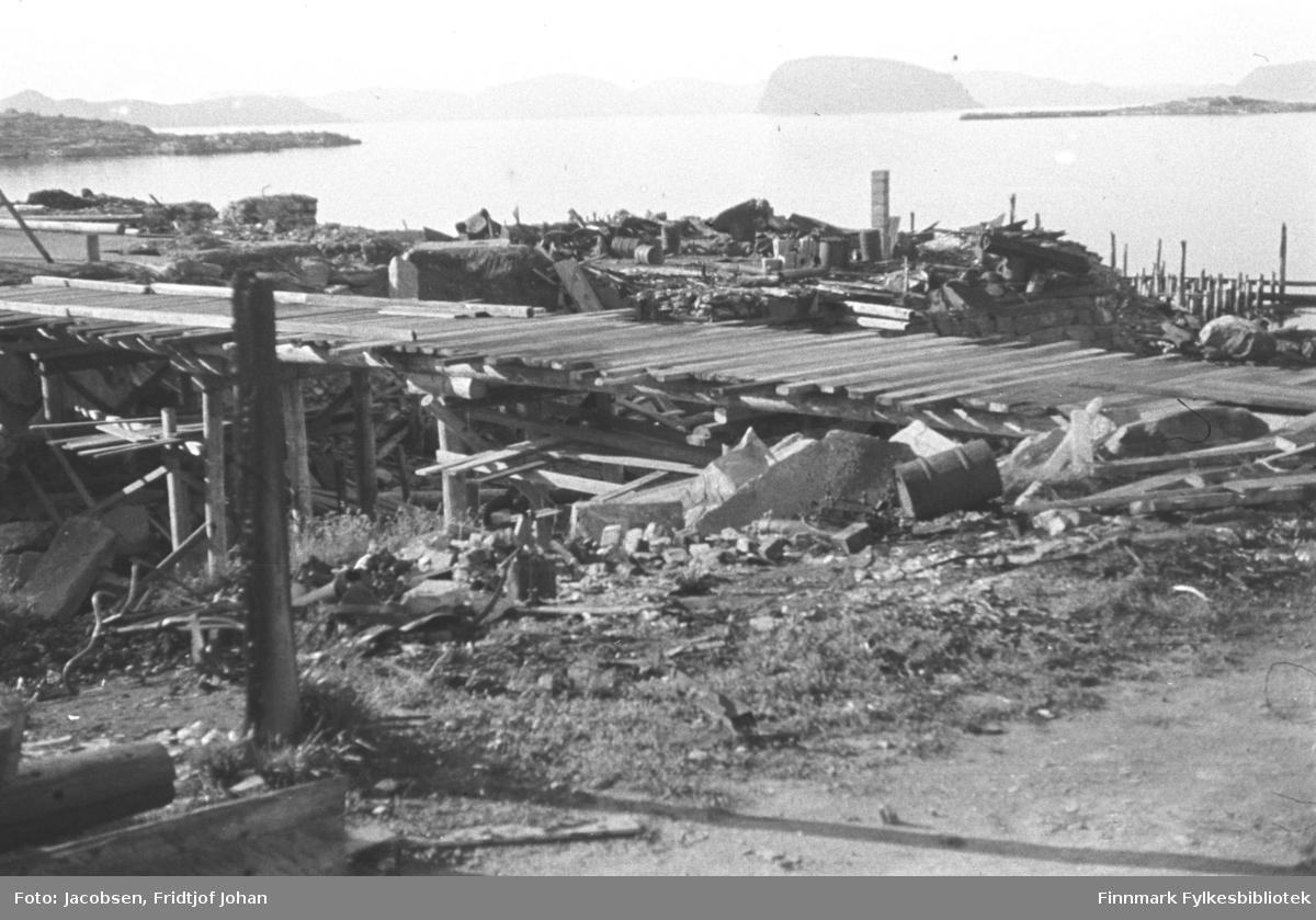 Provisorisk bru over Storelva. Sentrum ligger til venstre på bildet og bydelen Molla til høyre. Disse vises ikke på bildet. Brua har plankedekke og står på trepåler. Veien nederst på bildet, Skolebakken i dag, har grusdekke og det er litt gress og lyng. En tønne og andre rester fra ruinene ligger foran brua. En delvis brent stolpe står ned i bakken. Ruinene som ligger mellom sjøen og brua er Hauans materialhandel og stikkende ut i sjøen til høyre på bildet er restene av Hauankaia. Over den blikkstille havna ses Fuglenesodden med Øya Håja bak odden. Diffust i bakgrunnen ses Sørøya. Til venstre på bildet ses byodden og indre havn og over den ses øya Seiland. Bildet er nok tatt tidlig på sommeren 1945.