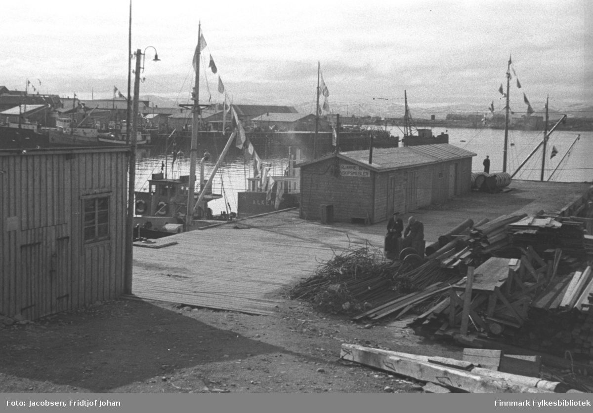 Bangkaia, den gamle dampskipskaia. Den ble ikke revet før i 2006. En avlang brakke står oppå og flere båter med flagg/vimpler ligger ved kaia. Stabler med material, stokker og armeringsjern ligger på siden av kaia.. To menn i ganske mørke klær står vedsiden av stablene og en mann står ytterst på Bangkaia. En brakke ses helt til venstre på bildet med en el-stolpe rett foran. På andre siden av den blikkstille havna ses Hammerfest-neset med kaier og større havnebygninger. Endel båter ligger langs kaiene. Oppe til høyre på bildet ses en del av Fuglenesodden.