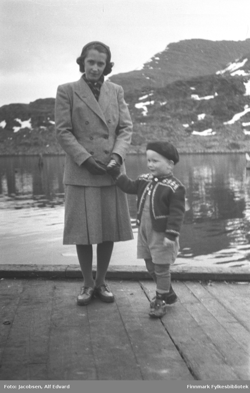 Aase Jacobsen og sønnen Arne fotografert på kaia i Havøysund. Aase har en ganske lys og ensfarget drakt med mørke knapper på seg. Hun har også svarte hansker, mørke sko og forholdsvis lys strømpebukse på meg. Hun holder Arne i hånda. Han har en alpelue på hodet, en mørk strikkejakke med lyst mønster på seg. På beina har han mørke sko og forholdsvis lys strømpebukse, shortsen og sjorta er enda litt lysere. Kaia de står på er av tre og en planke ligger på kanten som et slags rekkverk. Det er havblikk på havna og baugen på en båt ses helt til høyre på bildet. Nedre del er trefarget, rekka er hvitmalt og en ankerkjetting går fra baugen og ned i sjøen. På sjøen til venstre på bildet ses noe i sjøen, muligens en støtte eller et sjømerke. I bakgrunnen ses et fjellparti som er kupert og varierende i høyde. Det er stort sett stein og lite vegetasjon. Noen snøflekker ligger spredt rundt, som tyder på en vårdag.