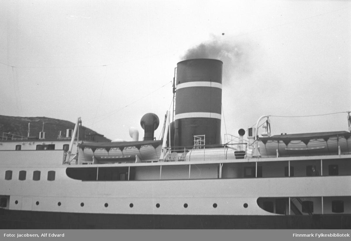 Hurtigruteskipet DS Sigurd Jarl til kai i Hammerfest. Det hvite overbygget har mange vinduer og ko-øyer langs siden. Deler av to ganger med tynne stolper ses langs nesten hele skipssiden. En mann står på den øverste. Den svarte skipssiden ses nederst på bildet. To livbåter med lyst skrog og mørkt trekk over står på toppen av overbygget. De hvite, buede festene/heisene står i hver ende av båtene. Der står også den høye skorsteinen. Den er mørk med påmalte striper. Det kommer litt røyk opp av den. Foran skorsteinen ses toppen av en luftekanal og bak en mye mindre. Til venstre på bildet ses toppen av et fjell.