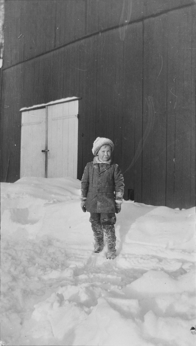 Iacob Ihlen Mathiesen som er fotografert foran en låve/driftsbygning. Guttenhar snø på klærne og snøen rundt ham er delevis måkt/opptråkket samt ren og fin. Det er vinter på Linderud Gård.