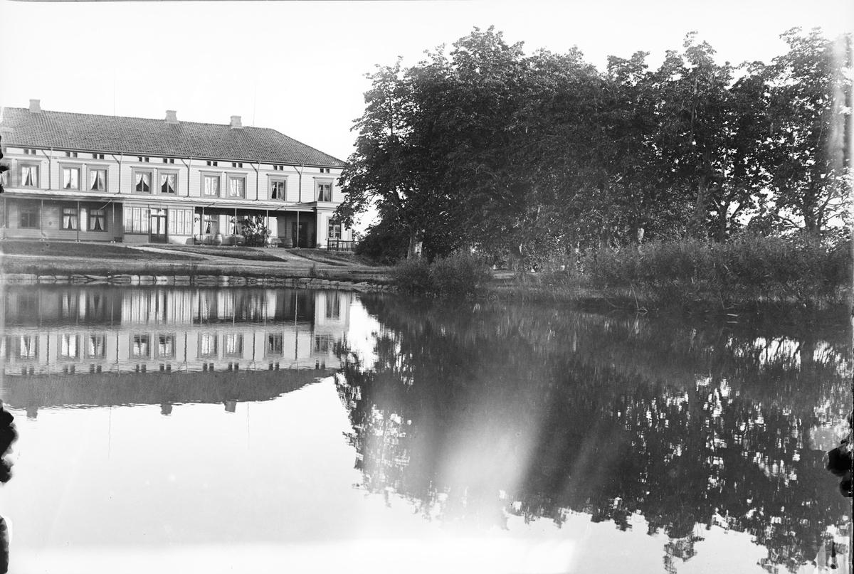 Dette bildet viser Linderud Gårds hovedhus og lindeallé som speiler seg i gårdens branndam/vannresserve. Vi ser inngangspartiet av huset med svalgang på begge sider av hoveddøren. Det er sommer på Linderud Gård.