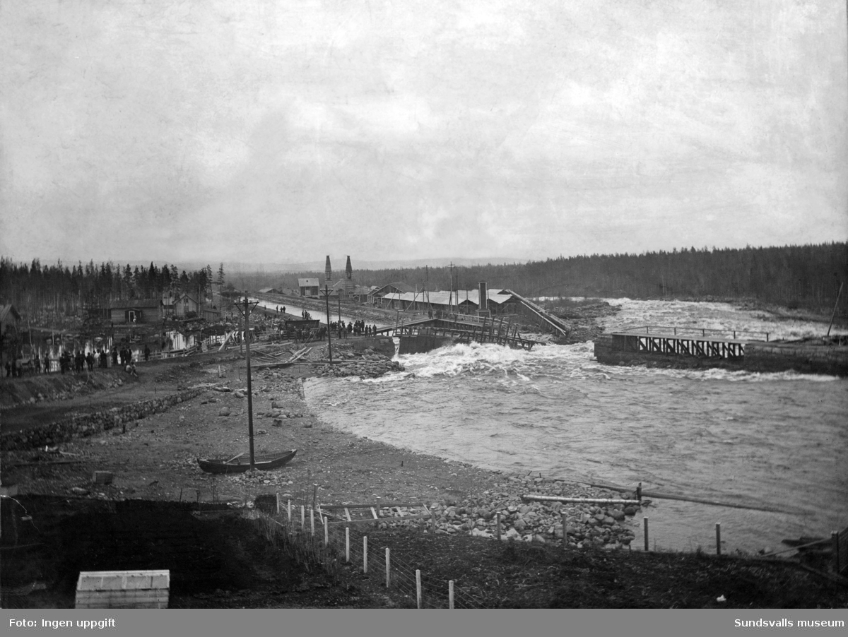 Alby kraftverksdamm våren 1906. En bristning i fördämningen har uppstått. I bakgrunden ses Alby karbidfabrik från 1901.