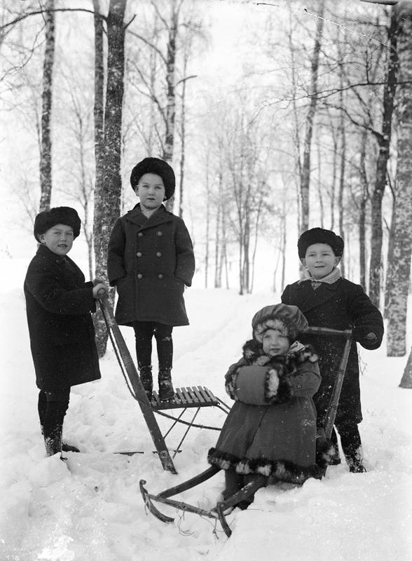Fyra barn med sparkstötting.Bröderna Olle och Lars Andersson och systern Britta ca 3 år gammal, samt deras kusin Börje Ramqvist från Västerås, son till deras faster Elin. Bilden bör vara tagen ca 1919. Givaren minns att en av sparkarna kom från Dalarna. Okänt var bilden är tagen men det bör ha varit i närheten av hemmet i Norberg.