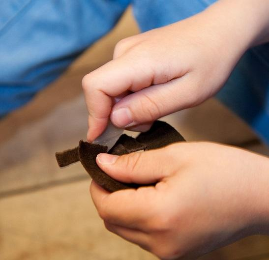 Nærbilde av barnehender som skjærer i en skinnbit med en steinflekke