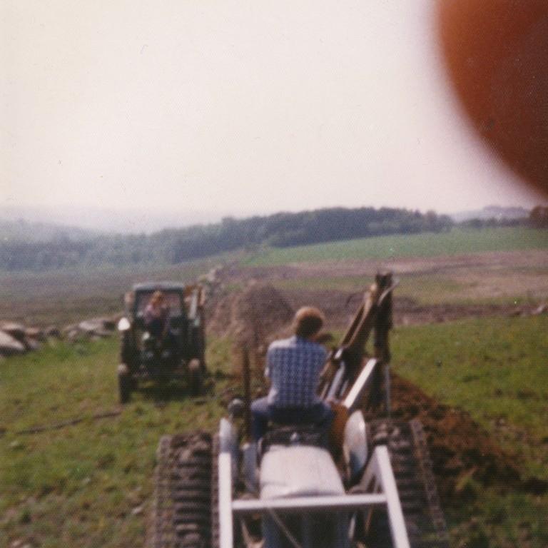 Dyrking på Mossige bruk 6. Lars Mossige på traktorgravaren med belte.