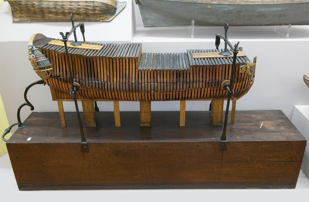 """Sektionsmodell av ett linjeskepp från 1738 Modellen består av olika sektioner som sammanhålles av 2 st """"skruvtvingar"""" fasta till en träsockel i form av en låda med järnhandtag. Modellen vilar å 3 st stöd med tumskala. Sockeln (lådan) mäter 1350X296X269 mm."""