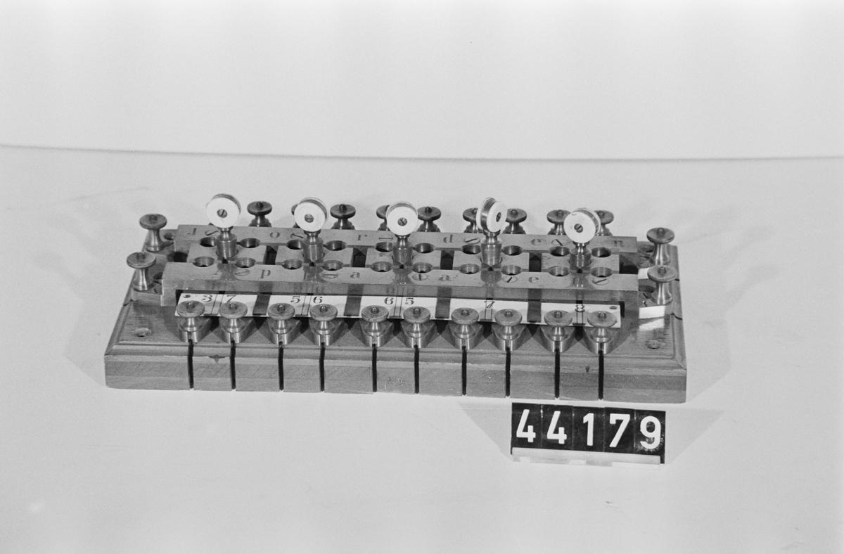 """Provskåpsplint för fem enkelledningar med jord- och apparatskenor. Text: """"Jorda- Apparaten"""" Märkt 19 på ena långsidan."""