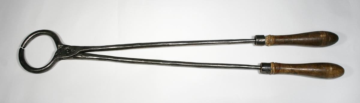 En lang tang i stål med trehåndtak. Selve klypen er sirkelformet.