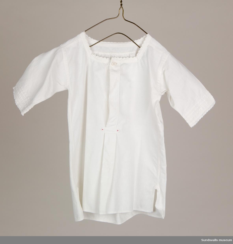 Ärmlös flickklänning i vit bomull med kantbrodyr och lagda veck.