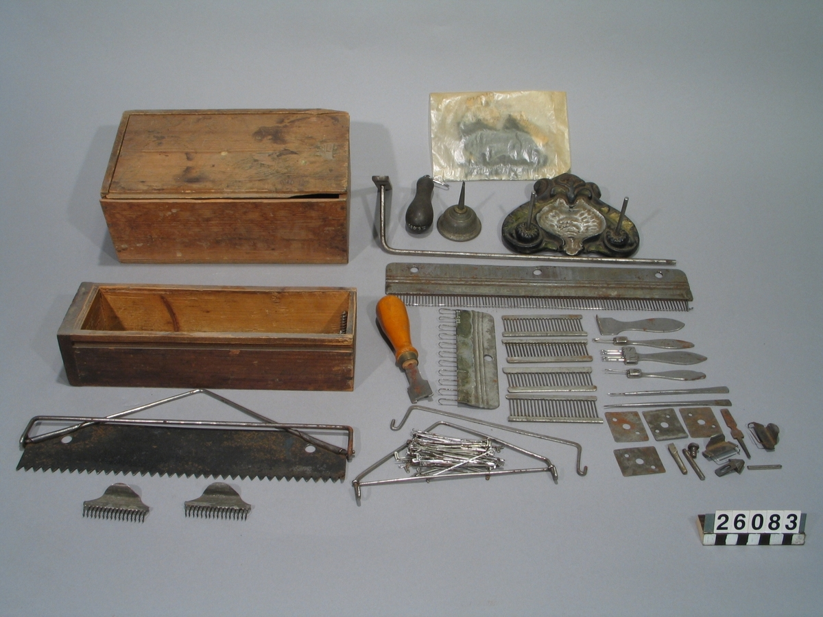 Stickmaskin, storlek nr. 9, för handdrift. Jämte tillbehör, i låda av trä. Tillbehör: Lösa delar: originallåda för transport (lock saknas), fästskiva av järn, bordsskiva av trä, 2 ben för skivan, maskinen, spolapparat, 4 (5, 1 spole lämnad av givaren 55-11-30. Skjutlåda för tillbehör, att placera på glidlister under bordsskivan, lämnad 1958-04-10). 2 vikthållare, 6 vikter, 1 päronformad vikt, garnställning, 2 större uppslagskammar, kam, arbetsfat för nålar m.m. med trådrullaxlar, nystvinda av trä, diverse smådelar i låda av trä, samt bruksanvisning, tryckt år 1900.