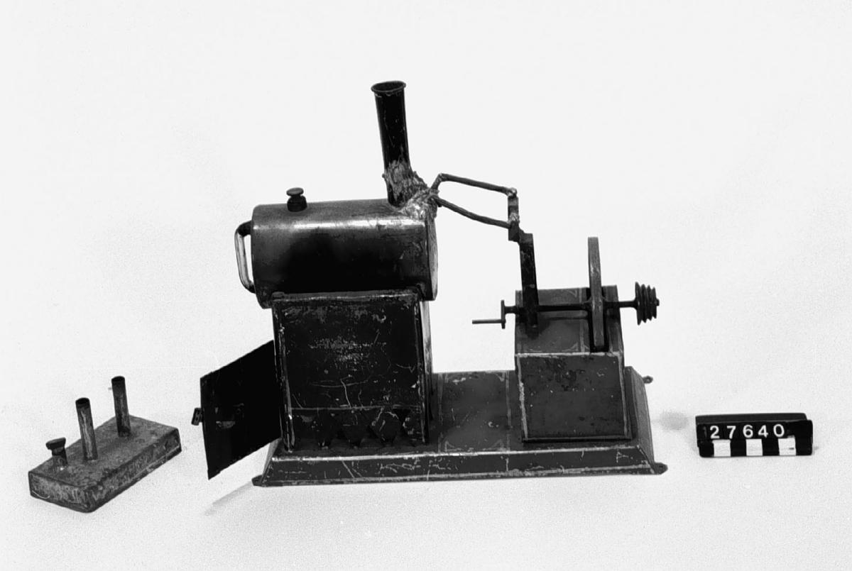 Liggande panna för spriteldning, med svänghjul med remskiva, på fundament av blålackerad plåt. Ångrören från pannan till sliden klumpigt lödda vid reparation. (troligen av givarens man, Einar Hogner). Tillbehör: Lösa delar:  maskin, spritlampa, påfyllningstratt(S). Cylinder, kolv och kolvstång saknas.
