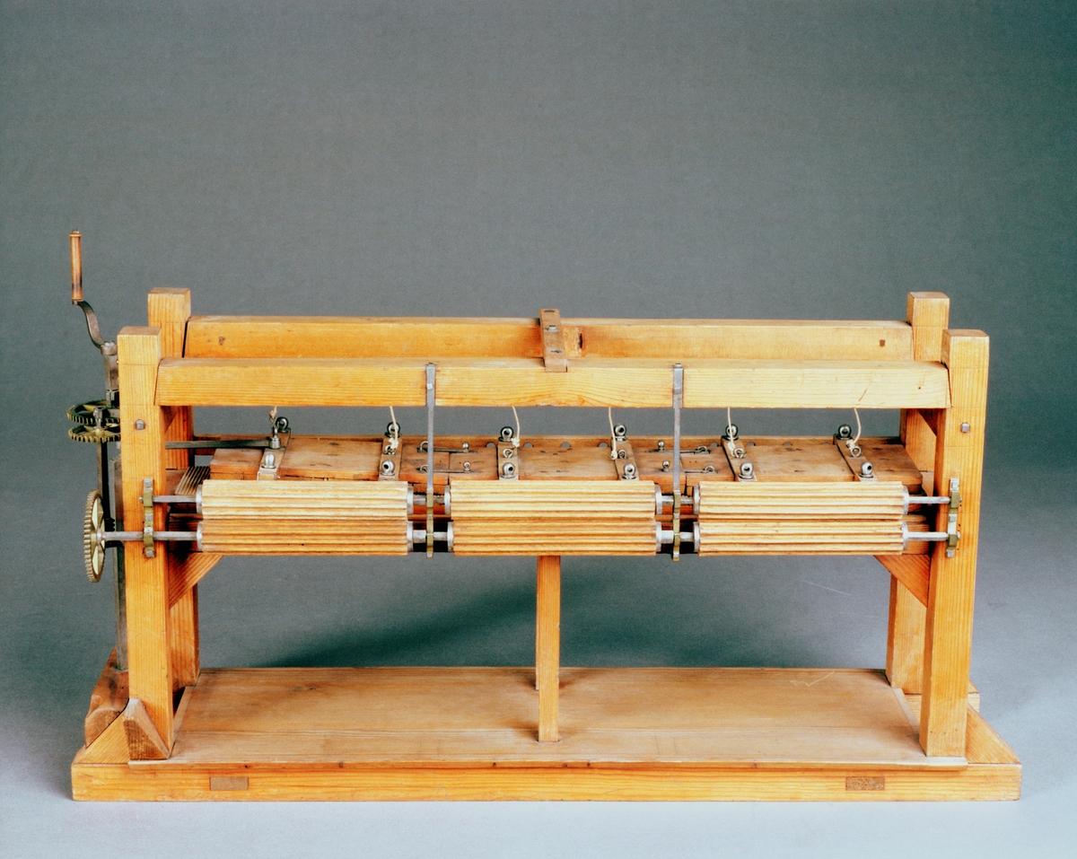 """Modell av appreturmaskin. Text på föremålet: """"III""""."""