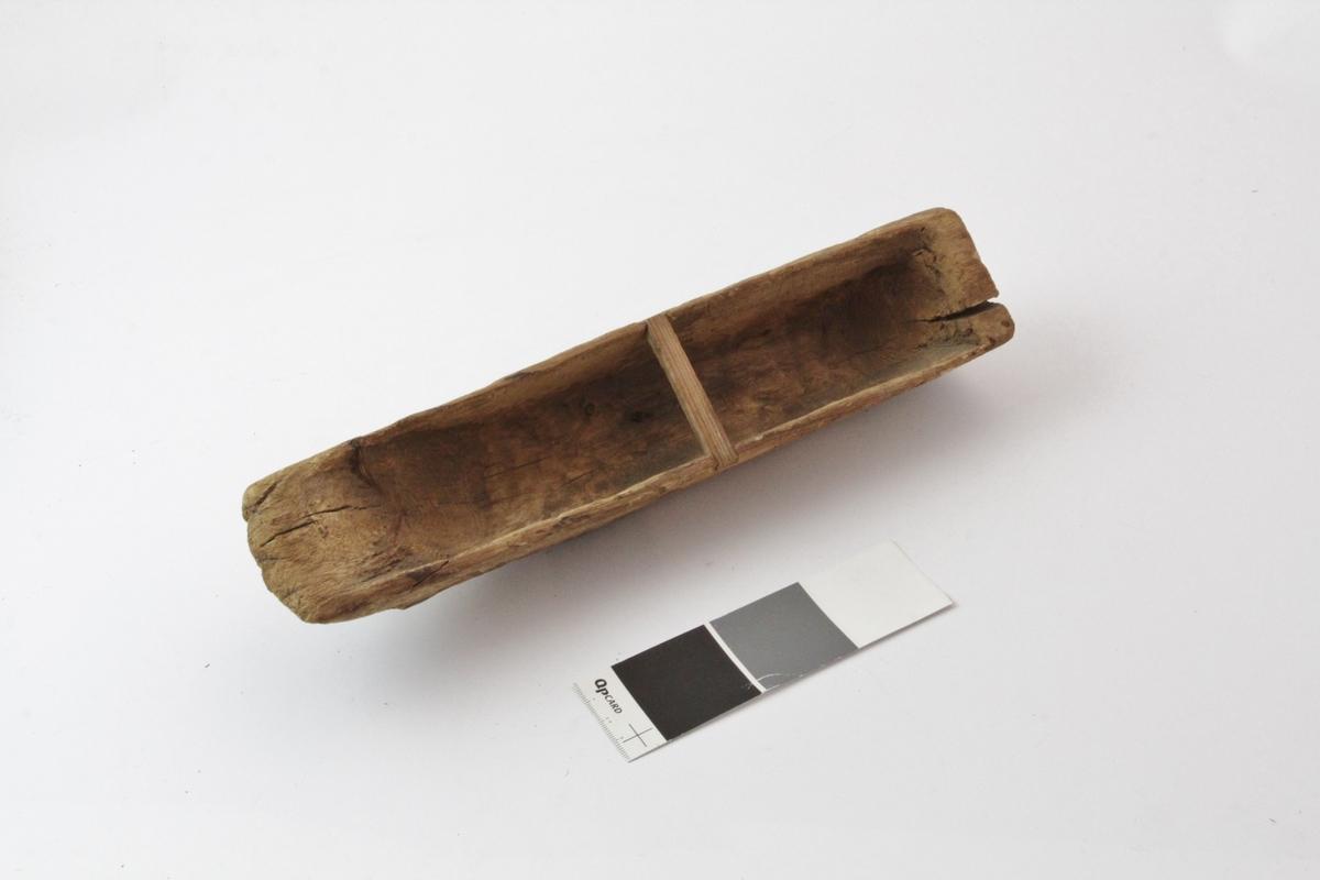 Lekebåt (ifølge tilvekstprotokoll) el. knega (ifølge T. Stuhaug ligner det). Gjenstanden har U-formet snitt og er utholet innvendig, skåret av et stykke tre. I ene kortenden rett avskåret, i den andre enden buet som en skitupp. Over utholing er det felt inn en trestav (liten) tvers over midten. På undersiden en smal jernstang på ene halvdelen, ene enden er festet med en jernkrampe, andre enden slått inn i kortenden.