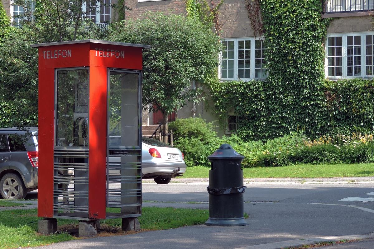 Denne telefonkiosken står i Jacob Alls gate/Schwachs gate på Majorstua. De røde telefonkioskene ble laget av hovedverkstedet til Telenor (Telegrafverket, Televerket) Målene er så å si uforandret.  Vi har dessverre ikke hatt kapasitet til å gjøre grundige mål av hver enkelt kiosk som er vernet.  Blant annet er vekten og høyden på døra endret fra tegningene til hovedverkstedet fra 1933. Målene fra 1933 var: Høyde 2500 mm + sokkel på ca 70 mm Grunnflate 1000x1000 mm. Vekt 850 kg. Mange av oss har minner knyttet til den lille røde bygningen. Historien om telefonkiosken er på mange måter historien om oss.  Derfor ble 100 av de røde telefonkioskene rundt om i landet vernet i 1997. Dette er en av dem.