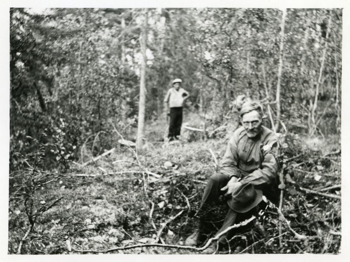 Portrett av en mann sittende i en skog. Mannen har en hatt på fanget og i bakgrunnen kan det ses en annen mann.
