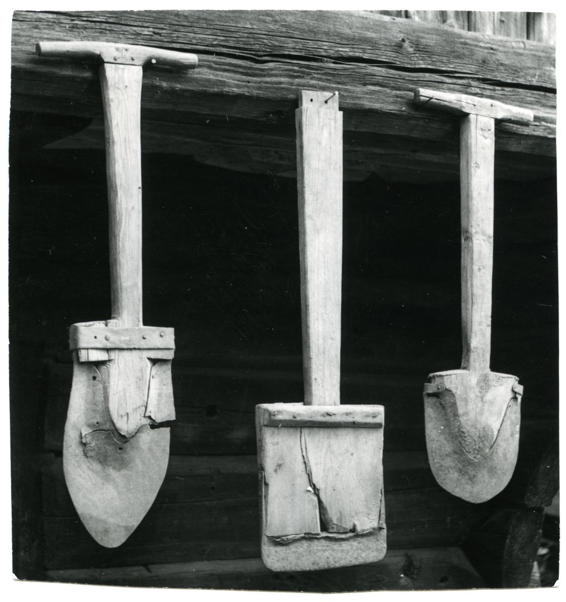 Tre spader henger fra en karm. Spaden til venstre er en såkalt stikkspade mens de andre er til å ta torv med.