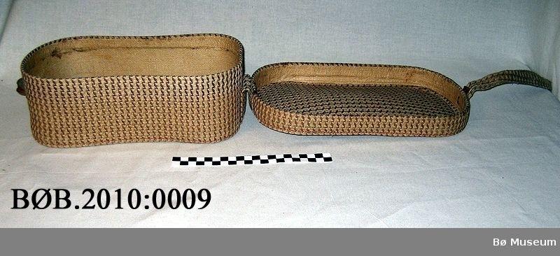 Form er rektangel med avrunda hjørne. Veska liknar ein hatteask. Det er eit handtak.